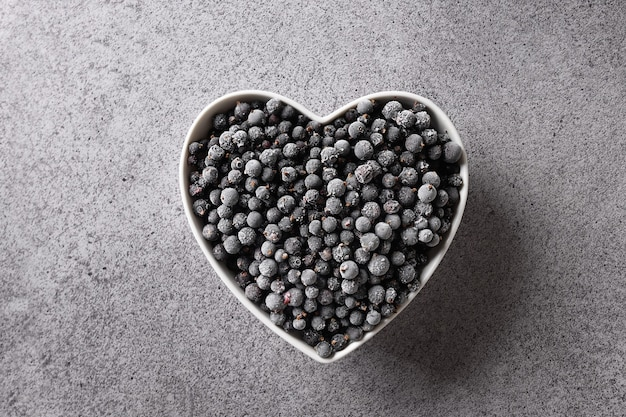 Frozen black currant in plate shaped as heart on a gray background view from above