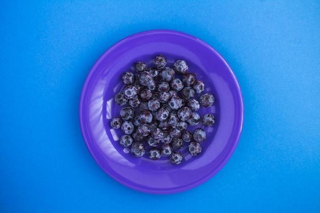 Замороженная черника в синей тарелке в центре синего фона. вид сверху. крупный план.