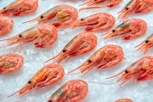 Frozen boiled shrimps lie on ice crumbs