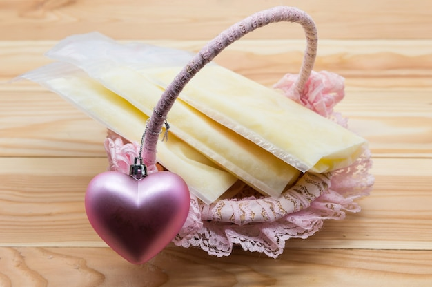 Frozen breast milk in storage bags on basket with pink heart on wood background with copy space for text. best nutrition food for baby newborn. pumping breastmilk for spared stock