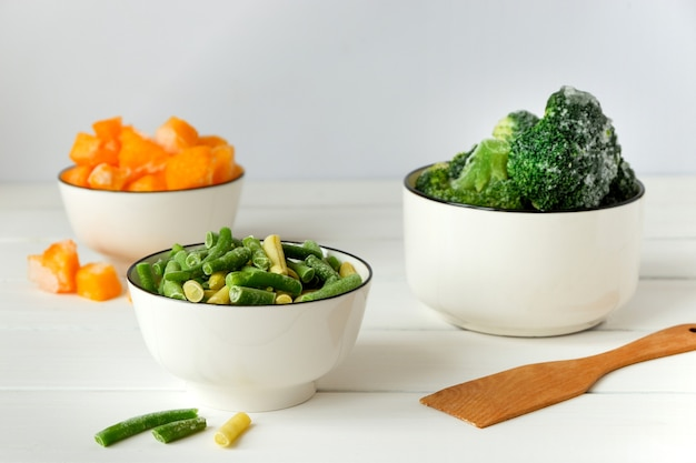 Frozen broccoli, french beans and pumpkin in white bowls on white table