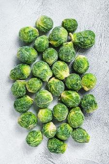 Замороженная брюссельская капуста зеленая капуста на кухонном столе. белый фон. вид сверху.