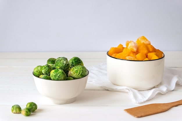 Frozen brussels sprouts and pieces of pumpkin in white bowls on white table