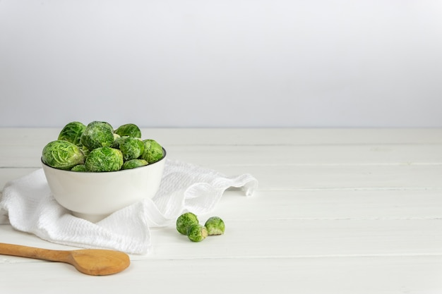 Frozen brussels sprouts in a white bowl with a wooden spoon on white table