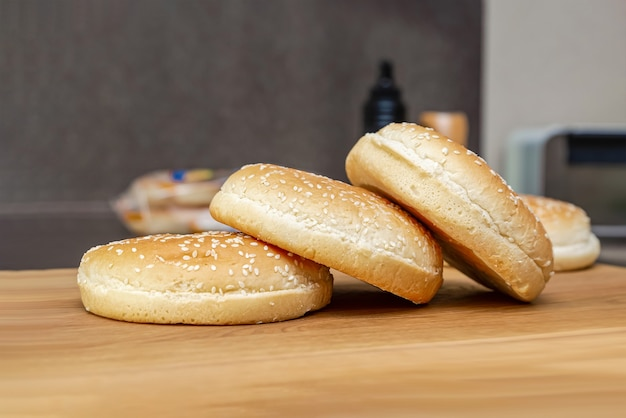 Замороженные булочки для бургера лежат стопкой на деревянной разделочной доске, процесс приготовления бургера на кухне дома.