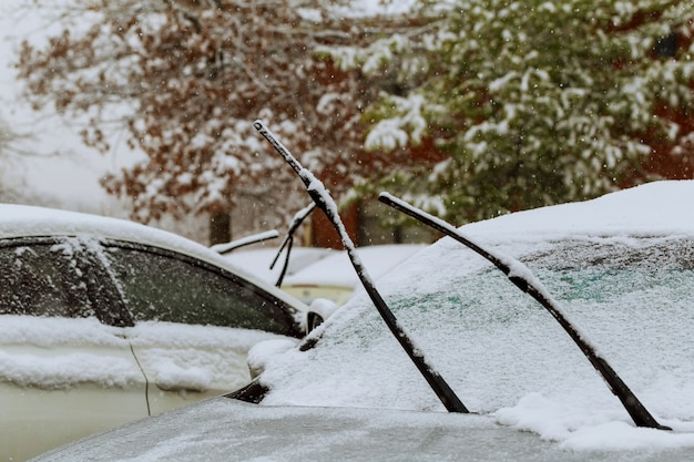 Frozen car covered snow at winter day, view front window windshield selective focus