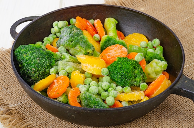Замороженная морковь с брокколи и зеленым горошком на сковороде