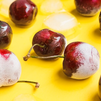 Frozen cherries on yellow background