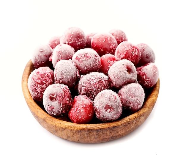 Замороженные ягоды вишни в деревянной тарелке.