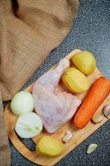 Frozen chicken on a wooden chopping board with vegetables to make chicken soup