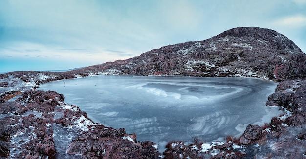 Frozen clear mountain lake, panoramic winter view