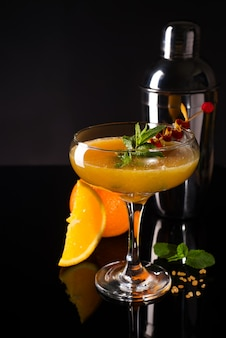 Frozen cocktail smoothie margarita with brownish sugar and mint on a black glass background