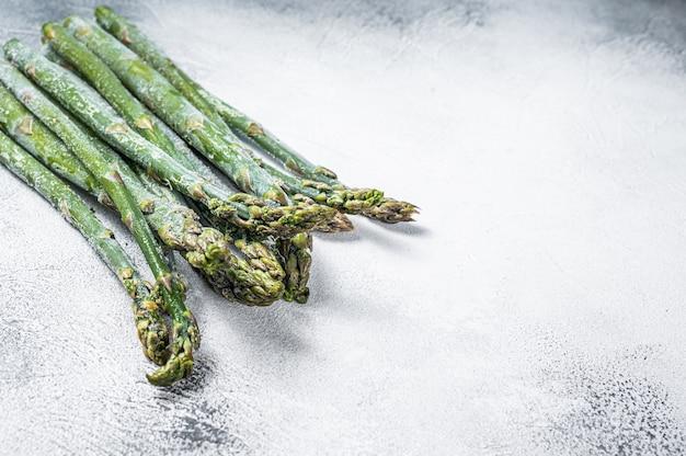 오래된 식탁에 냉동된 차가운 아스파라거스. 흰 바탕. 평면도. 공간을 복사합니다.