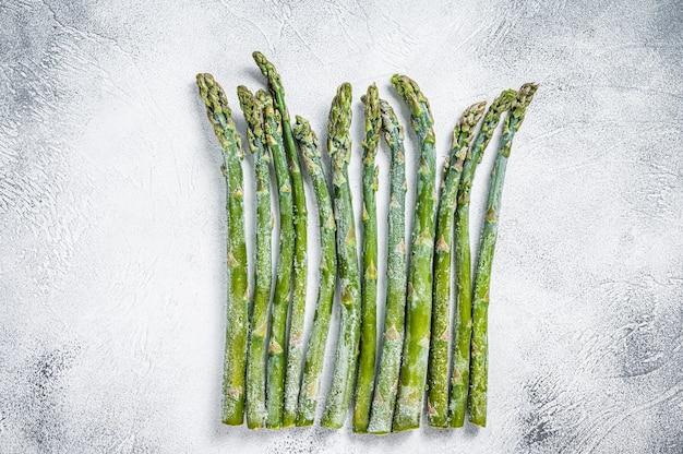 오래된 식탁에 냉동된 차가운 아스파라거스. 흰 바탕. 평면도.