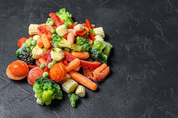 Замороженные холодные нарезанные овощи, брокколи, сладкий перец, помидоры, морковь, горох и кукуруза. черный фон. вид сверху. скопируйте пространство.