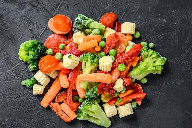 Замороженные холодные нарезанные овощи, брокколи, сладкий перец, помидоры, морковь, горох и кукуруза. черный фон. вид сверху.