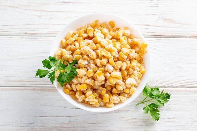 Замороженная кукуруза в тарелке на белом деревянном столе