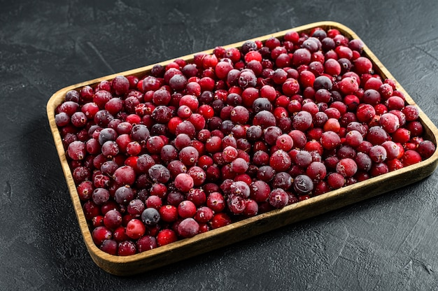 Frozen cranberries in a wooden bowl. black background. top view
