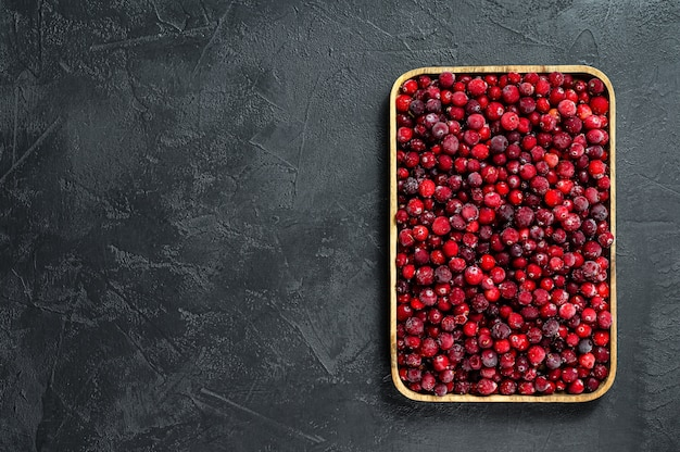 Frozen cranberries in a wooden bowl  black surface    surface