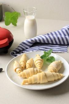 하얀 접시에 냉동 크루아상, 아침 식사로 크루아상 와플 또는 크로플을 만드는 준비.