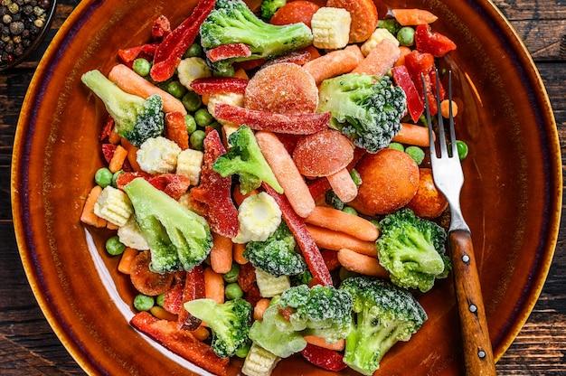 Замороженные нарезанные овощи, брокколи, сладкий перец, помидоры, морковь, горох и кукуруза на тарелке. темный