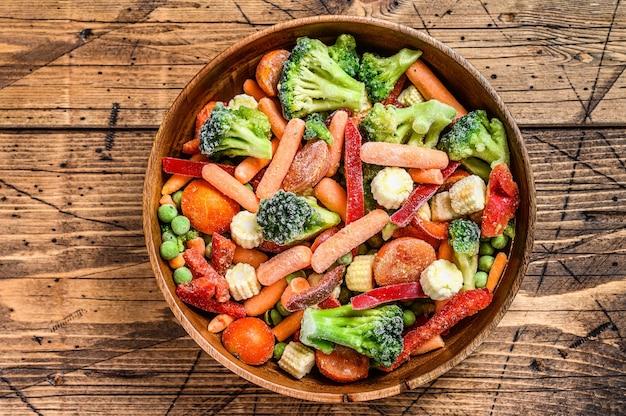 Замороженные овощи, брокколи, сладкий перец, помидоры, морковь, горох и кукуруза. деревянный фон. вид сверху.