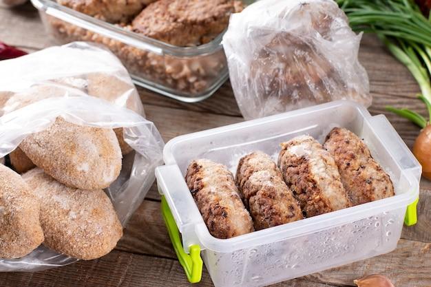 먹을 준비가 된 나무 테이블에 비닐 봉지에 냉동 커틀릿 또는 미트볼