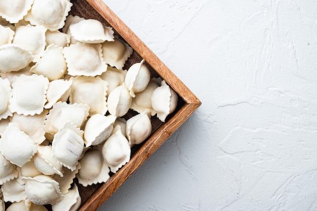 Замороженные пельмени тортеллини и равиоли в деревянной коробке, на белом столе, плоская планировка, вид сверху, с copyspace