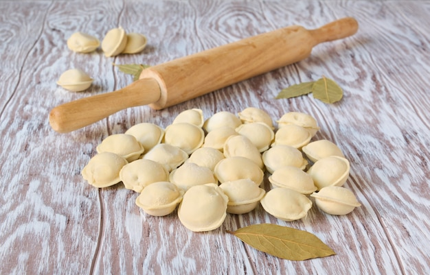 Frozen dumplings and wooden rolling pin on wooden table, close up