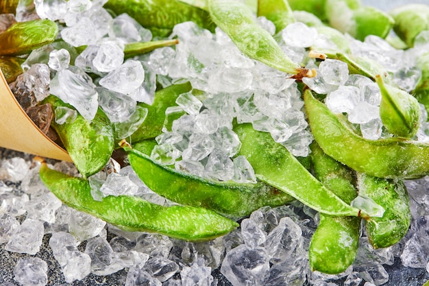 Frozen edamame or soybeans in the mix with crushed ice on a blue background