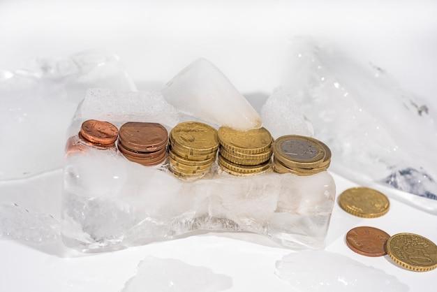 Замороженные монеты евро во льду