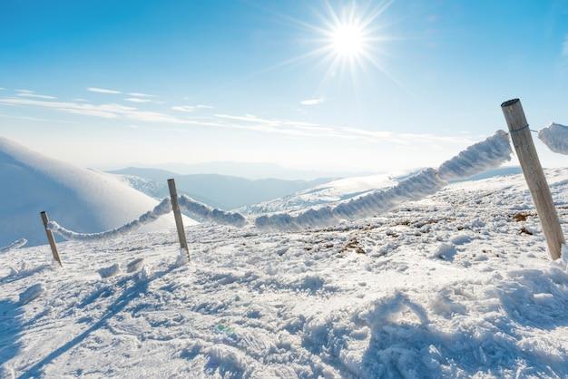冬の高山の村の氷と雪で凍った柵。山の風景
