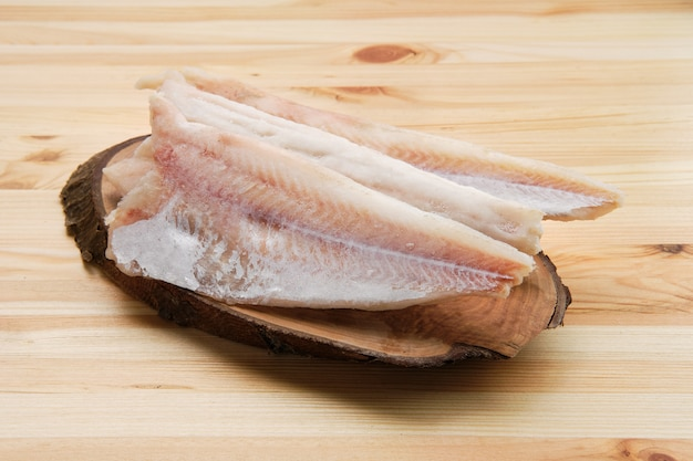 Frozen fillet of pangasius on wooden table