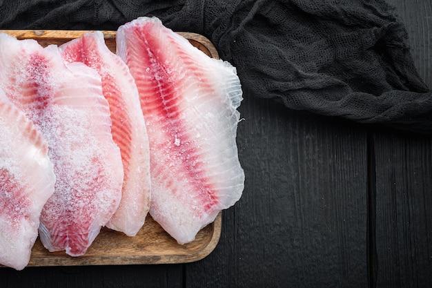 Набор замороженного рыбного филе, на черном деревянном столе, вид сверху