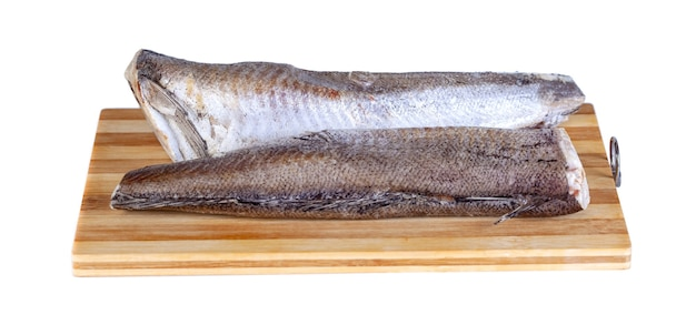 Frozen fish hake on the wooden board isolation on white