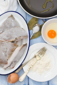 Frozen fish with egg, powder on wooden