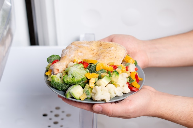 냉동실에있는 냉동 식품. 접시에 고기와 야채를 냉동. 냉동 식품, 장기 보관 제품의 개념. 프리미엄 사진
