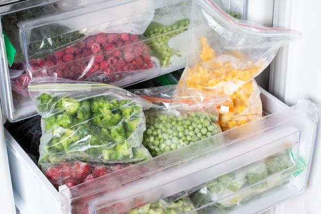 冷凍庫で冷凍食品。冷凍野菜、冷凍庫での調理済みの食事。冷凍肉、食品、野菜。食料貯蔵庫