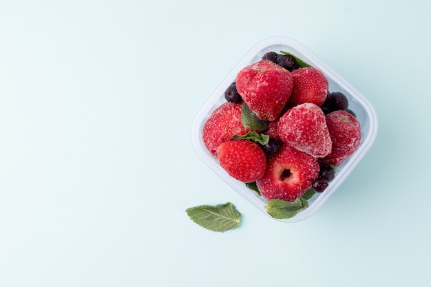 Frozen food. strawberry berries on a blue space. copy space