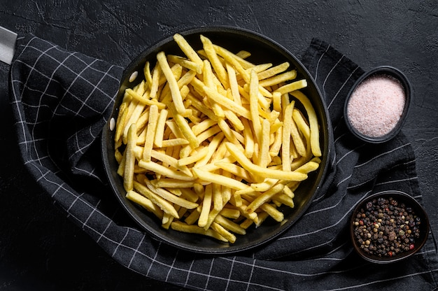Frozen french fries in a frying pan. top view