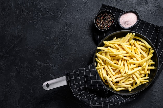 Frozen french fries in a frying pan.