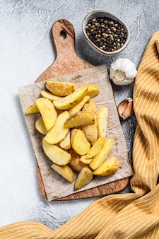 Frozen french fries potato wedges on a wooden cutting board