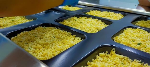 Замороженный жареный рис с яйцом в пластиковом лотке в ожидании верхней печати этикетки с помощью термоформовочной машины на пищевой фабрике. замороженная пищевая промышленность. процесс готовой еды в производстве. пищевая упаковочная промышленность.
