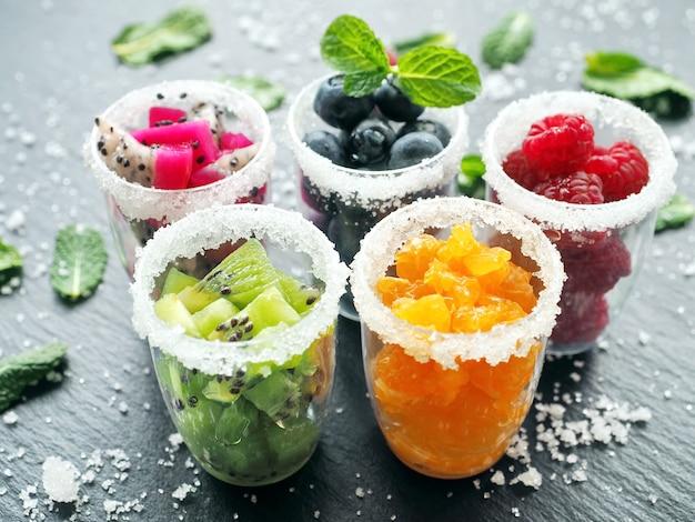暗い表面のガラスの冷凍果物とベリー