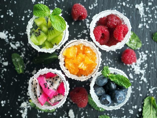 グラスに砂糖を入れた冷凍フルーツとベリー