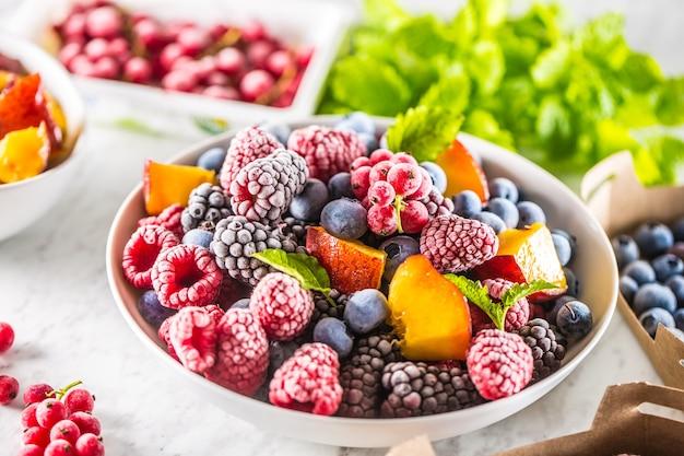 Замороженные фрукты черника ежевика малина красная смородина персик и зелень мелисса.