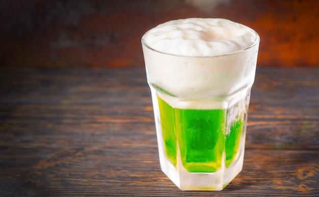 古い暗い机の上に緑色のビールと大きな泡の頭が付いた冷凍ガラス。飲み物と飲み物のコンセプト