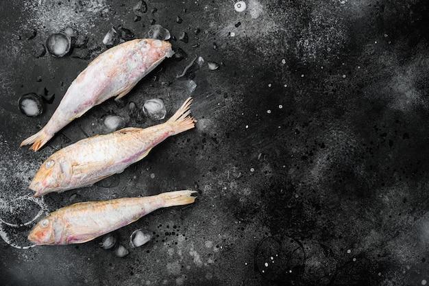 冷凍ヒメジ生魚セット、黒い暗い石のテーブルの背景、上面図フラットレイ、テキストのコピースペース