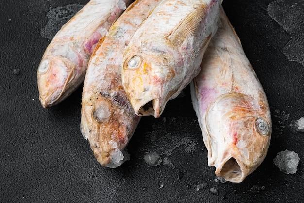 검은 어두운 돌 테이블 배경에 냉동 염소고기 생선 세트
