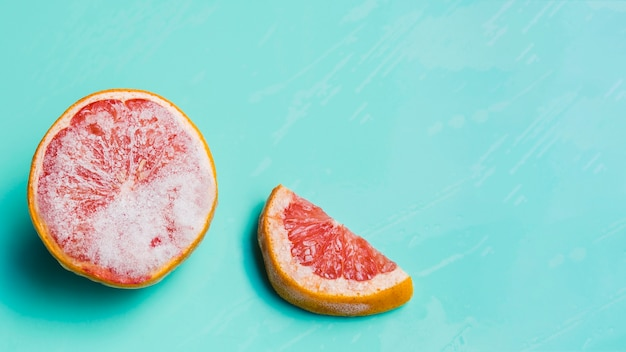 Frozen grapefruit on turquoise background